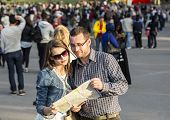 Couple With A Map In A Crowded City
