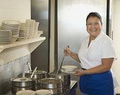 stock photo of ladle  - Hispanic waitress ladling soup - JPG