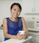 Asian woman holding coffee mug