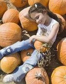Hispanic girl laying in pumpkin patch