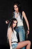 stock photo of gun shot wound  - two white girls with handguns on black background - JPG