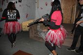 MUSKOGEE, OK - Sept. 13: Runners with guns hunt zombies in an abandoned house during the Castle Zomb
