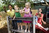 pic of daycare  - Diverse group of preschool 5 year old children playing in daycare with teacher - JPG
