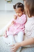 Little girl playing with beads on her mother�?�¢??s laps
