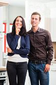 Man and woman buying domestic kitchen in studio or furniture store