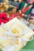 Christmas present wrapped in gold paper against a background of blurred gifts