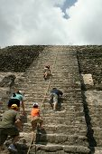 Tourists Climbing Mayan High Temple Ruins in Lamanai, Belize