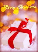 Closeup photo of little white gift box with red ribbon on blurry lights background, Merry Christmas greeting card, wintertime holidays concept