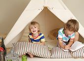 foto of teepee  - Child preschooler kids playing at home indoors with a teepee tent - JPG