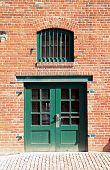 Green Door And Window In Brick Wall