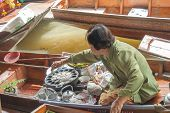 A Woman Makes Thai Food At Damnoen Saduak Floating Market