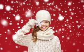 winter, people and happiness concept - smiling girl in hat, scarf and gloves with big snowflake