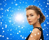 people, holidays, christmas and glamour concept - beautiful woman in evening dress wearing earrings over blue snowy background