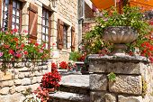 Bright Flower Pots On An Ancient Stone House In France