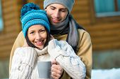 Half-length portrait of hugging couple drinking tea outdoors during winter vacations