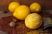 Lemons, nutmegs and grater on paper on wooden background