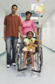 stock photo of pre-adolescents  - African girl smiling in wheelchair with parents in hospital - JPG