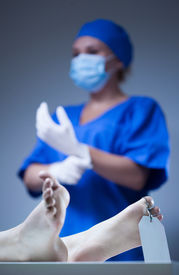 stock photo of autopsy  - Nurse and dead body in morgue vertical - JPG