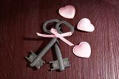 Keys with decorative hearts on wooden background