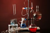 Fixed laboratory glassware on support on dark colorful background