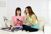 Two girls  with decorative cosmetics on home interior background