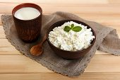 Cottage cheese in bowl with cup of milk on wooden background