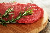 Raw beef steak with rosemary on cutting board on wooden background