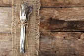 Silverware tied with rope burlap cloth and rustic wooden planks background