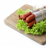 Smoked thin sausages  with lettuce salad leaves on wooden cutting board, isolated on white