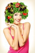 Beautiful young woman with vegetable wig isolated on white