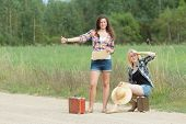 Students hitchhikers with cardboard on road