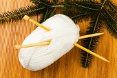 Roll Of White Soft Knitting Yarn And Yew Branch