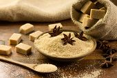foto of sugar  - brown sugar cubes in burlap sack sugar with star anise in a bowl - JPG