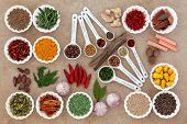 Herb and spice selection in measuring spoons and crinkle bowls.