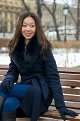 beautiful Asian girl in winter coat on the bench