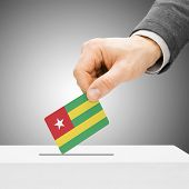 Voting Concept - Male Inserting Flag Into Ballot Box - Togo