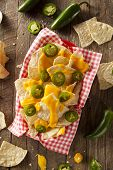 stock photo of jalapeno  - Homemade Nachos with Cheddar Cheese and Jalapenos - JPG