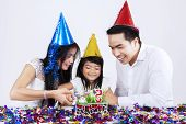 Portrait Of Asian Family Cutting A Cake