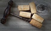 Antique Corkscrew With Used Corks On Aged Wood