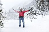 foto of jacket  - Happy young man with a red jacket and snow glasses throws up snow - JPG