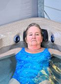 picture of hot-tub  - Mature female blond beauty relaxing in her hot tub outdoors - JPG