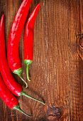 stock photo of red hot chilli peppers  - red hot chilli peppers on the wooden table - JPG