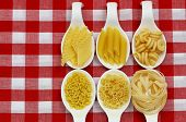 Uncooked pasta on spoons on checkered cloth with copy space