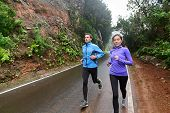 Healthy lifestyle people running on country road exercising. Runners jogging on mountain road training for marathon. Asian woman and Caucasian man wearing waterproof sports clothing for wind and rain.