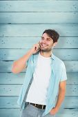 Happy casual man talking on phone against wooden planks