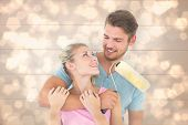 Young couple hugging and holding paint roller against light glowing dots design pattern