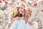 Smiling couple embracing and looking against grey valentines heart pattern