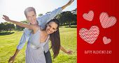 Happy couple with arms outstretched at park against cute valentines message