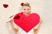 Attractive young blonde showing red heart against white wall