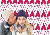 Attractive couple in winter fashion against valentines day pattern